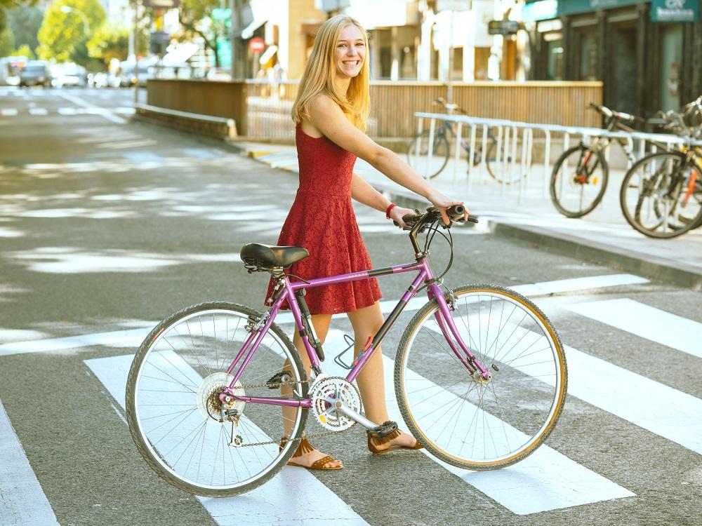Uśmiechnięta dziewczyna na rowerze miejskim